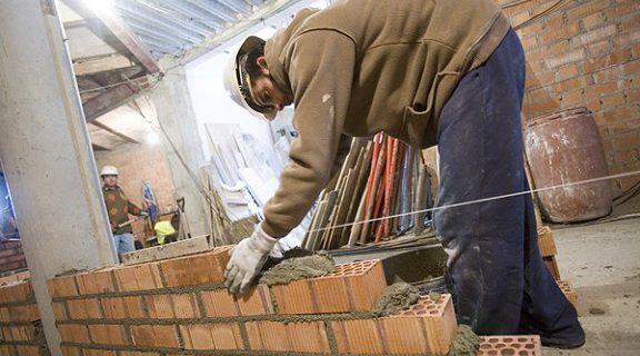 Un treballador de la construcció aixecant una paret | Adrià Costa